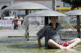 Người dân Hungary tìm cách giải nhiệt tại một đài phun nước ở trung tâm Budapest.