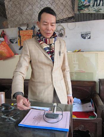 Ông Trần Quang Thiều thử nghiệm độ nhạy của  chiếc bẫy chuột bằng tờ giấy thay vì con chuột.