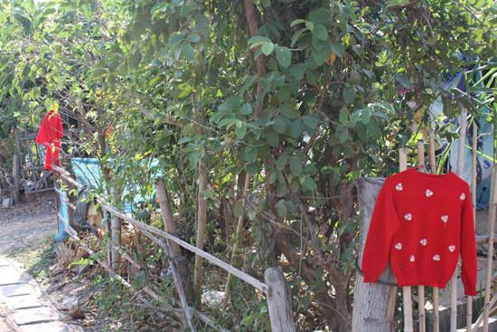 Những chiếc áo đỏ được treo phía trước những ngôi nhà trong một làng ở tỉnh Surin, Thái Lan để xua đuổi ma.
