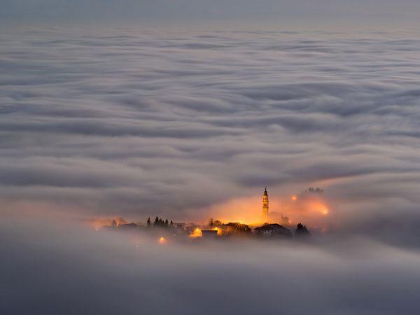 Thị trấn Asiago Plateau (Italia) chìm trong mây phủ khi được nhìn từ một đỉnh núi gần đó