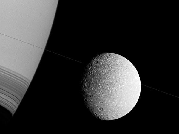 """Ảnh vũ trụ: Sao Thổ """"nhìn trộm"""" mặt trăng Dione"""