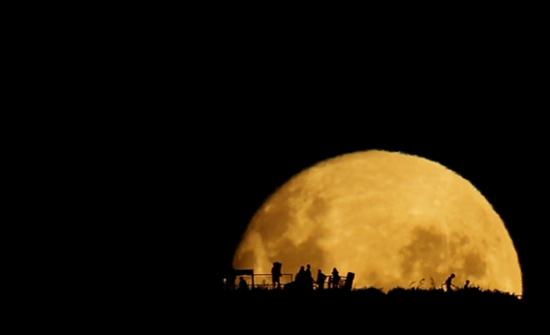 Mặt trăng khổng lồ nhô lên khỏi đường chân trời.