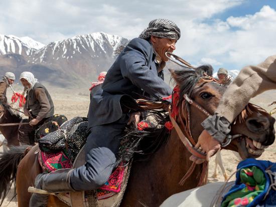 Ngậm chiếc roi da trong miệng, một người đàn ông Kyrgyz đang điều khiển con ngựa của mình trong một trò chơi truyền thống có tên gọi là Buzkashi, một cuộc thi tương tự như môn polo, ngoại trừ việc người ta thay quả bóng bằng một con dê không có đầu.