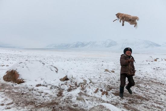 Một cậu bé tinh nghịch đang tung hứng con mèo của mình tại một khu trại mùa đông của gia đình cậu, gần biên giới giữa Afghanistan với Tajik.