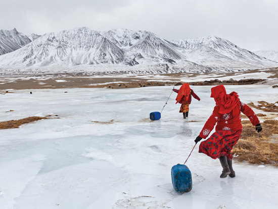 Hai cô gái Kyrgyzstan đang kéo những chiếc can nhựa đựng nước trên lớp băng trơn của một dòng sông để trở về gia đình.