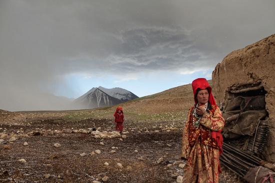 Hai người phụ nữ mạo hiểm bước ra ngoài túp lều trét bằng bùn đất của họ sau một cơn mưa đá lớn tại một khu vực cắm trại mùa thu bên cạnh sông Aksu.