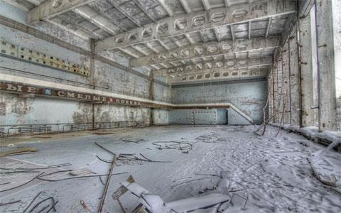 Một phòng thi đấu thể dục thể thao bị bỏ hoang, với lớp tuyết phủ nhẹ trên mặt đất.