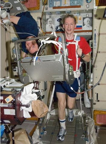 Frank de Winne chạy trên băng chuyền trong một khoang của ISS để duy trì cơ bắp và thể lực.
