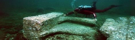 Một nhà khảo cổ đang đo đạc bức tượng bằng đá granit đỏ.