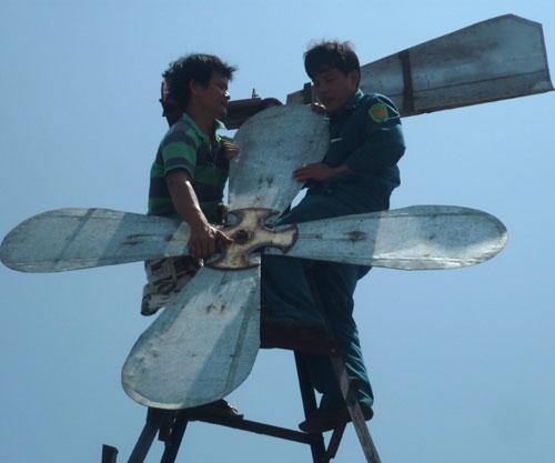 Anh Trần Thanh Thành (trái) điều chỉnh quạt gió trên nóc nhà