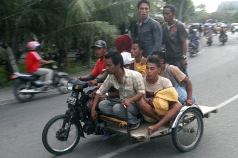 Những người đàn ông này lại chọn xe xích lô gắn máy để chạy trốn sóng thần.