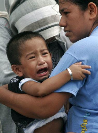 Một bé trai òa khóc vì sợ hãi khi được mẹ bế đi sơ tán ở Aceh.