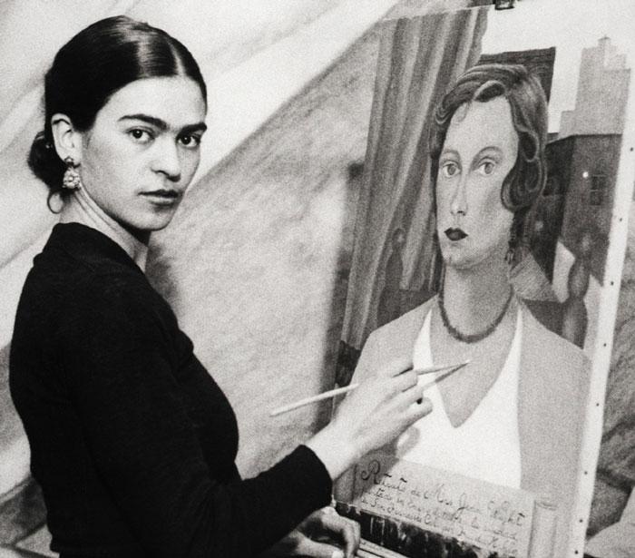 Frida Kahlo bên một tác phẩm tự hoạ