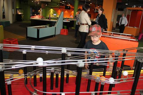 Cậu bé thích thú thả bóng và theo dõi chuyển động của bóng theo đường ray trong Trung tâm Questacon.