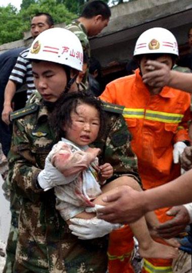 Một em bé mình mẩy xây xát và dính máu được nhân viên cứu hộ bế ra khỏi đống đổ nát ở Nhã An.