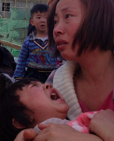 Một người mẹ bế đứa con trong cơn hoảng loạn do động đất.