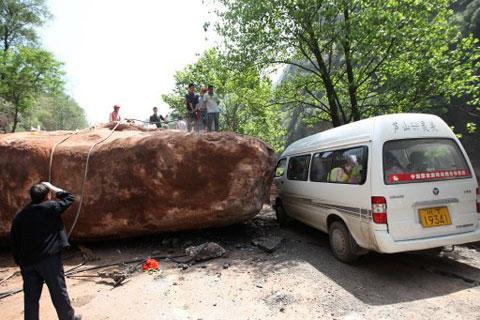 Người dân ở Longmen cùng nhau cố sức đẩy một tảng đá lớn trên đường. Nó lăn xuống trong trận động đất sáng nay.