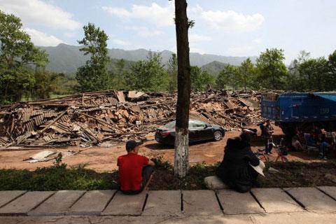 Người dân ở Longmen ngồi nhìn nhà cửa của mình nay đã biến thành một đống đổ nát sau trận động đất sáng 20/4.