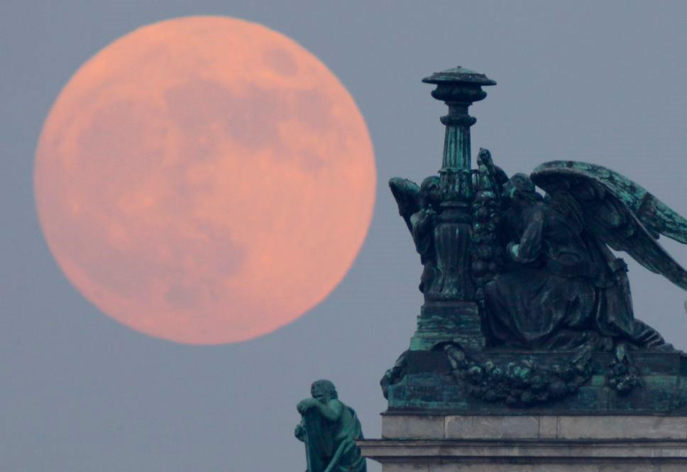 Mặt trăng màu đỏ sau tượng thiên thần trên nhà thờ St. Isaak ở St.Petersburg, Nga.