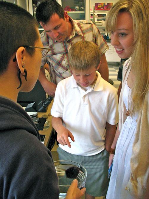 Một nhà nghiên cứu đang cho chị em Caroline Roy xem con nhím biển