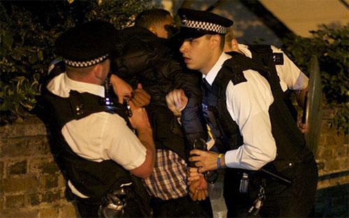 Cảnh sát bắt một phần tử gây bạo loạn tại quận Camden, thành phố London vào tối 8/8. (Ảnh: AP)