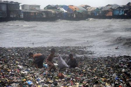 Các em bé nhặt nhạnh những thứ còn có thể sử dụng được trong một bãi rác ở khu ổ chuột gần vịnh Manila hôm nay, phía sau là những con sóng lớn do ảnh hưởng của siêu bão Nanmadol. (Ảnh: AFP)