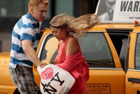 Gió mạnh hất tung tóc và đồ của các du khách ở thành phố New York. Trước khi bão đến, cả thành phố đã được báo động, các hệ thống giao thông ngừng một phần hoặc toàn bộ hoạt động. Trước cửa thị trường chứng khoán nổi tiếng của thành phố, hàng loạt bao cát được đặt sẵn để đề phòng nước lụt tràn vào. (Ảnh: AFP)