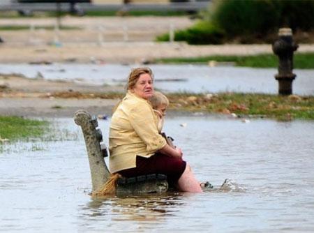 Một phụ nữ cùng một cậu bé với vẻ mặt lo âu ngồi trên một chiếc ghế đá giữa biển nước lũ ở bờ biển Rockway, thành phố New York. (Ảnh: AFP)