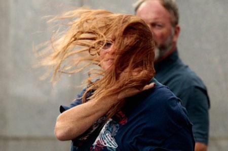 """Gió thổi bay tóc một phụ nữ trên phố ở Lower Manhattan, New York. Tuy không mạnh bằng dự báo, cơn bão Irene vẫn còn """"rất nguy hiểm"""", như lời cảnh báo của Tổng thống Mỹ Brrack Obama, bởi nó mang theo gió lớn và gây ngập lụt. (Ảnh: AFP)"""