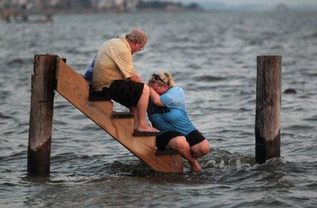 Hai cha con ngồi an ủi nhau ở nơi từng có căn nhà gỗ của họ tại bang Bắc Carolina ngày 28/8. (Ảnh: AFP)