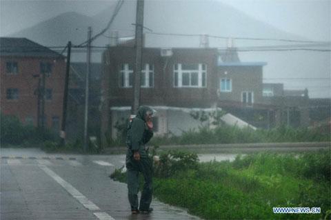 Một người đàn ông đang chống chọi cơn gió mạnh tại thị trấn Hepu, huyện Xiangshan. Ít nhất 130 người sống ở nông thôn bị cô lập.