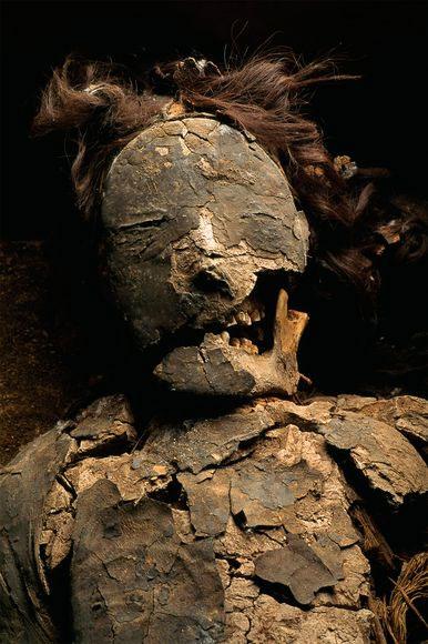 Xác ướp đang mỉm cười với bộ tóc giả và được phủ bởi lớp tro đen 5.000 năm tuổi.