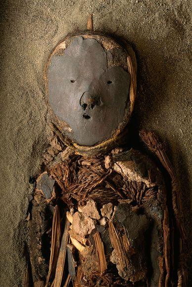 Một xác ướp trẻ em Chinchorro được dán mặt nạ trên đỉnh hộp sọ.