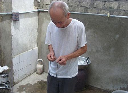 Ông Trần Huy Hoàng đang tìm mạch nước với 2 thanh sắt được cầm trên tay.