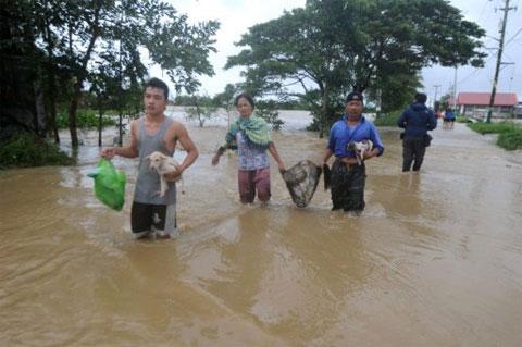 Người dân tại vùng lụt ở Calumpit, Bulacan, phía bắc thủ đô Manila đang đi tản hôm 28/9. (Ảnh: AFP)
