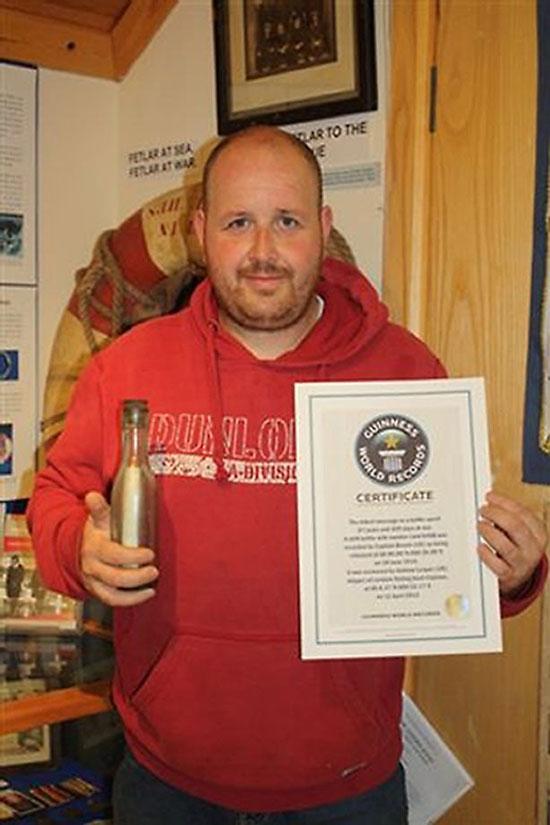 Andrew Leaper cầm chiếc chai chứa thông điệp cổ nhất và giấy chứng nhận của Sách Kỷ lục thế giới Guinness.