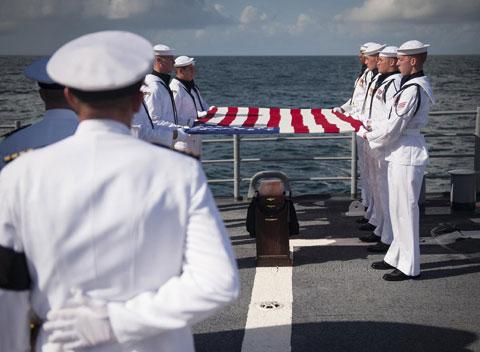 Các binh sĩ trên hàng không mẫu hạm thực hiện các nghi lễ đám tang dành cho quân nhân như trải quốc kỳ, nổ súng và tấu kèn tiễn biệt.