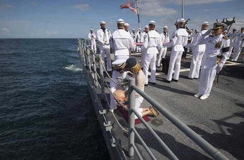 Sĩ quan chỉ huy hàng không mẫu hạm cùng bà Carol Armstrong thả bình đựng tro cốt của nhà du hành xuống đại dương. NASA không công bố vị trí của tàu trong ảnh theo nguyện vọng của gia đình Armstrong. Nơi mà USS Phillipine Sea neo đậu là cảng Mayport, bang Florida.