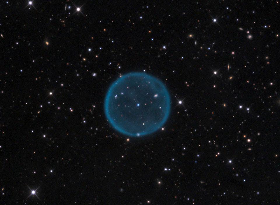 Tinh vân cầu Abell 39 thoạt nhìn giống như một bóng ma. Nó rộng 5 năm ánh sáng và nằm gọn trong Ngân Hà và cách chúng ta 7000 năm ánh sáng về phía chòm sao Hercules. Abell 39 là một tinh vân hành tinh hình thành sau khi một ngôi sao cỡ Mặt trời phát nổ hàng nghìn năm trước, đồng thời để lại ở trung tâm của nó một ngôi sao lùn trắng. Cấu trúc tròn đơn giản của nó lại là manh mối rất tốt cho các nhà thiên văn tìm hiểu thành phần hoá học và vòng đời của các ngôi sao. Nền trời phía sau của thiên hà có thể nhìn rõ xuyên qua tinh vân mờ ảo này.
