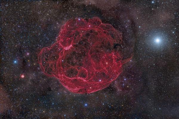 Tàn tích Simeis 147 của một vụ nổ sao siêu mới này cách chúng ta 3000 năm ánh sáng, rộng 150 năm ánh sáng và trải rộng bằng 6 Mặt trăng tròn trên bầu trời. Bên trái hình là ngôi sao Elnath thuộc chòm sao Kim Ngưu. Màu đỏ được làm nổi lên cho thấy bức xạ của khí hydro. Vụ nổ đã xảy ra khoảng 4 vạn năm trước và để lại không chỉ đám mây này mà còn một ngôi sao neutron hoặc một pulsar ở trung tâm.