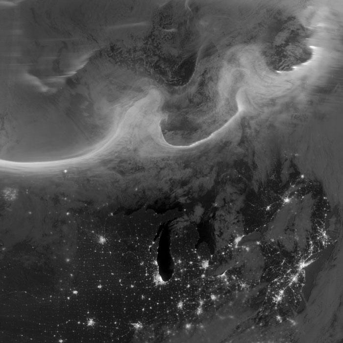 Nhìn từ vệ tinh Suomi-NPP, chúng ta có thể dễ dàng nhận ra lục địa Bắc Mỹ vào ban đêm với ánh sáng từ các thành phố lớn như Chicago, Toronto, Montreal, Quebec, NewYork, Boston, Philadelphia.... Phần trên của bức ảnh chính là bắc cực quang bao quanh vùng cực và trải rộng ra các vĩ độ thấp hơn, có nguyên nhân từ các cơn bão địa từ, gây ra bởi sự phát xạ mạnh của Mặt trời vào hồi đầu tháng. Tấm màn ánh sáng ở độ cao hơn 100km, được tạo ra do các phần tử mang điện được gia tốc trong từ quyển kích thích các phân tử khí oxy và nito trên thượng tầng khí quyển.