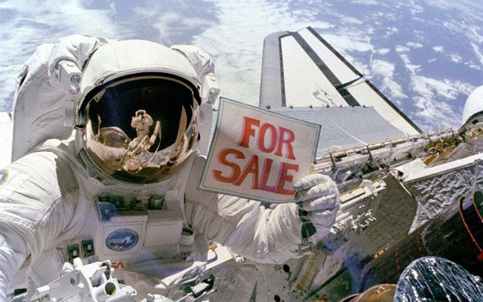 Phi hành gia Dale A. Gardner trong không gian va phi hành gia Joseph P. Allen phản chiếu trong tấm kính của mũ du hành.