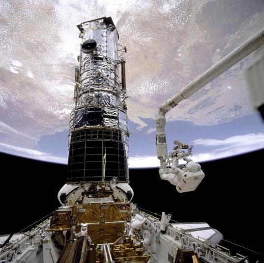 Phi hành gia Story Musgrave (trên) và Jeffrey Hoffman (dưới) đáp xuống vị trí của kính viễn vọng không gian Hubble cỡ lớn.