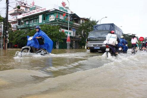 Quốc lộ 1A đi qua thành phố Huế bị ngập sâu, nước chảy xiết.