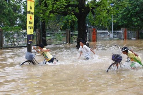 Dường như đã quen với lũ, đám học trò lại phấn khích khi lội nước.