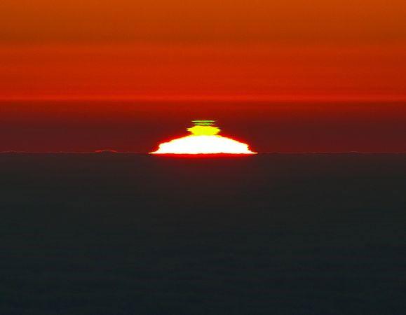 """Hình ảnh chụp gần đây ở ngọn núi Cerro Paranal cao 2.600m ở sa mạc Atacama (Chile) cho thấy hai hình cung màu xanh riêng biệt trên Mặt trời đang lặn. Hiện tượng hiếm này xảy ra khi ánh nắng Mặt trời bị """"bẻ cong"""" là tách thành nhiều màu sắc khác nhau do từ trường của Trái đất."""