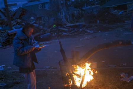 Một người dân đốt lửa sưởi ấm gần ngôi nhà bị bão phá hủy của mình ở New York.