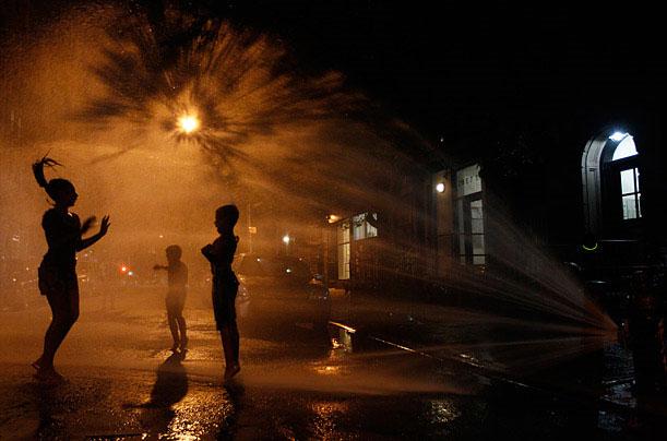 Trẻ em đang tắm mát ở một vòi nước cứu hỏa khi nhiệt độ ở New York đạt đến 38°C vào tháng7/2011.