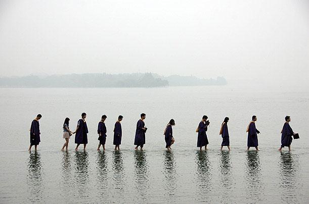 Sinh viên đại học đi bộ qua một công viên ngập nước trong đợt lũ lụt ở Wuhan, Trung Quốc vào ngày 21/6/2011.