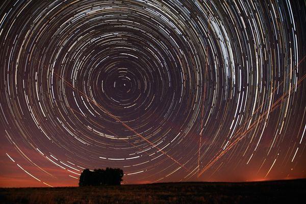 Ánh sáng của máy bay dương như cắt những vệt sao chạy hình tròn trong bức ảnh được chụp ở khu vực Alentejo, Bồ Đào Nha.